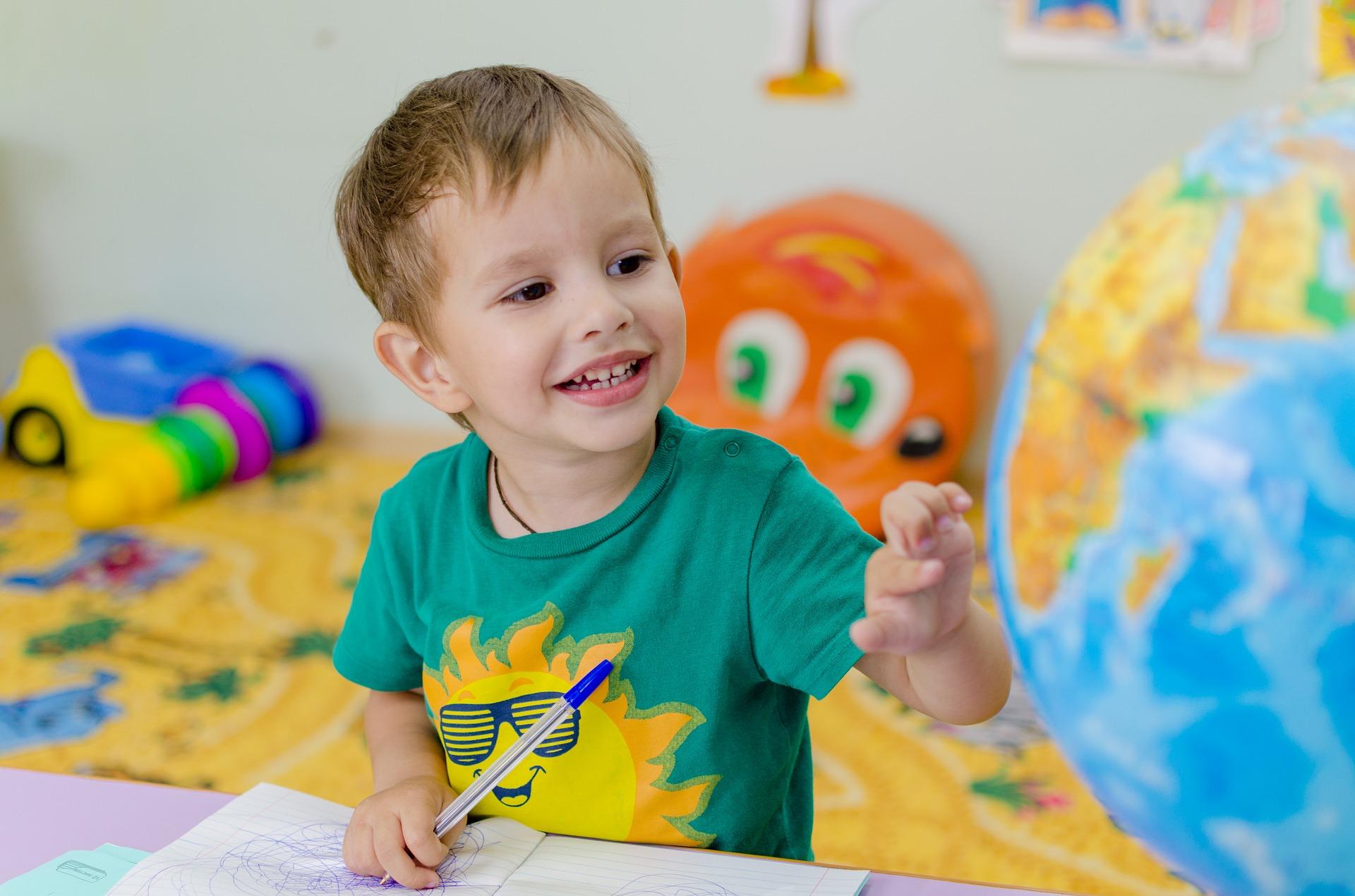 Enfant souriant en train de dessiner