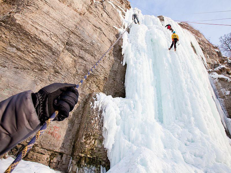 Ado pratiquant l'escalade sur glace en colo
