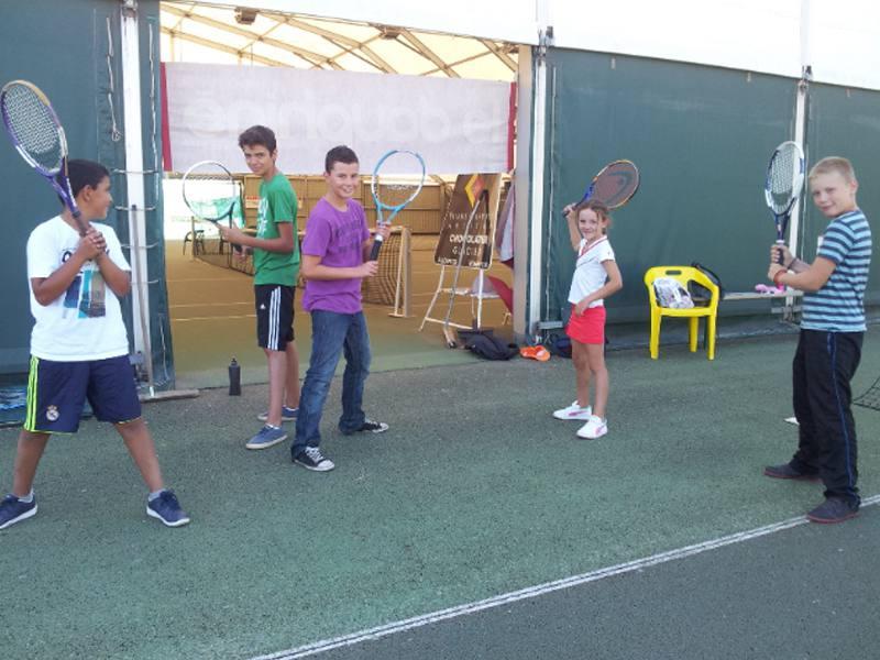 Groupe de préados jouant au tennis en colonie de vacances sportive en ardèche