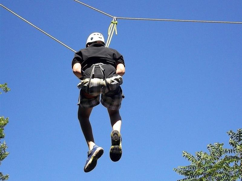 Adolescent pratiquant la descente en tyrolienne en colonie de vacances escalade été ardèche