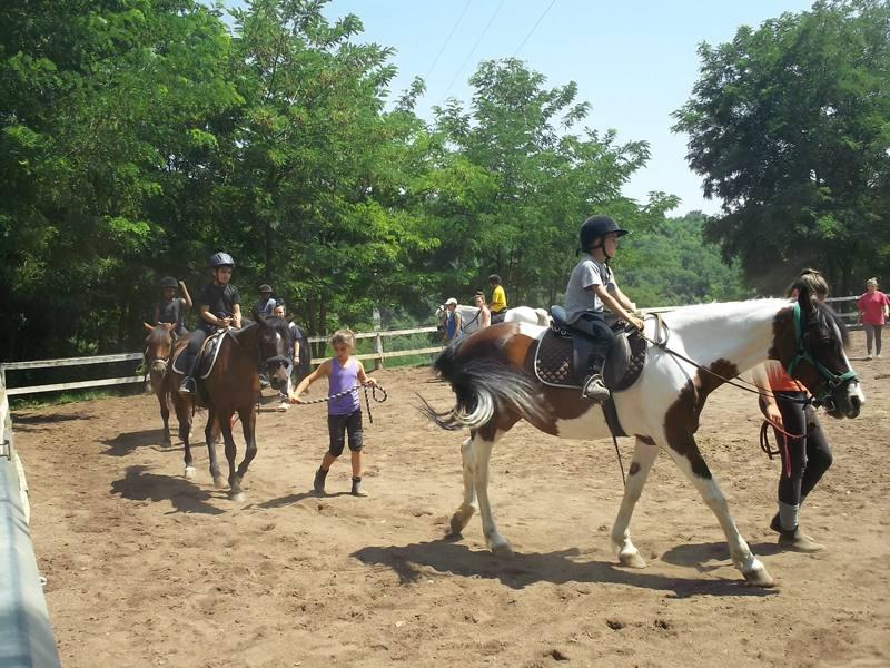 enfants faisant du cheval en colonie de vacances d'été