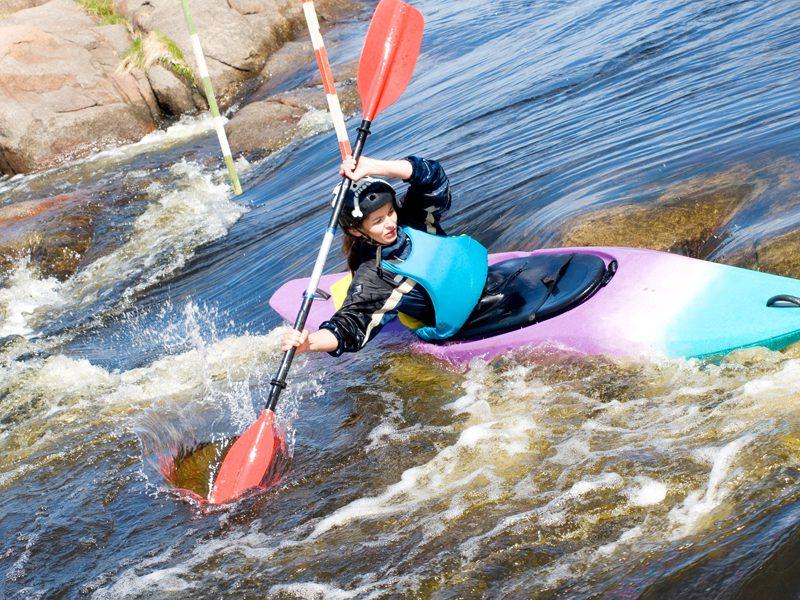 Adolescent faisant du canoe kayak en colonie de vacances d'été