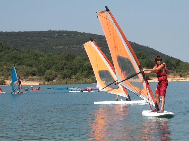 adolescents faisant de la planche à voile en colonie de vacances d'été