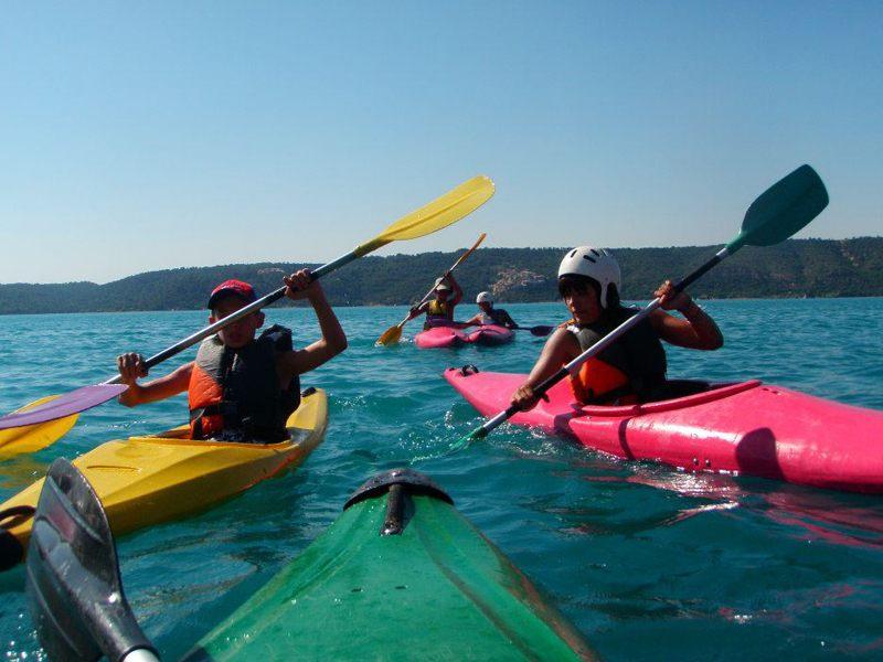 enfants et adolescents faisant du canoe kayak en colonie de vacances d'été
