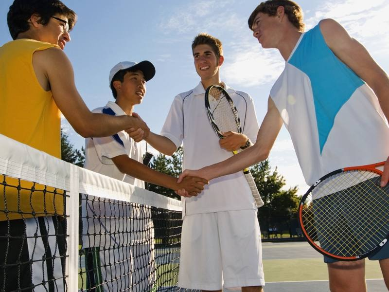 adolescents se serrant la main en colonie de vacances tennis