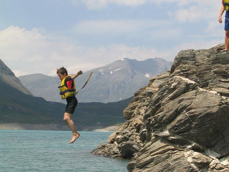 enfant plongeant en colonie de vacances d'été multiactivités