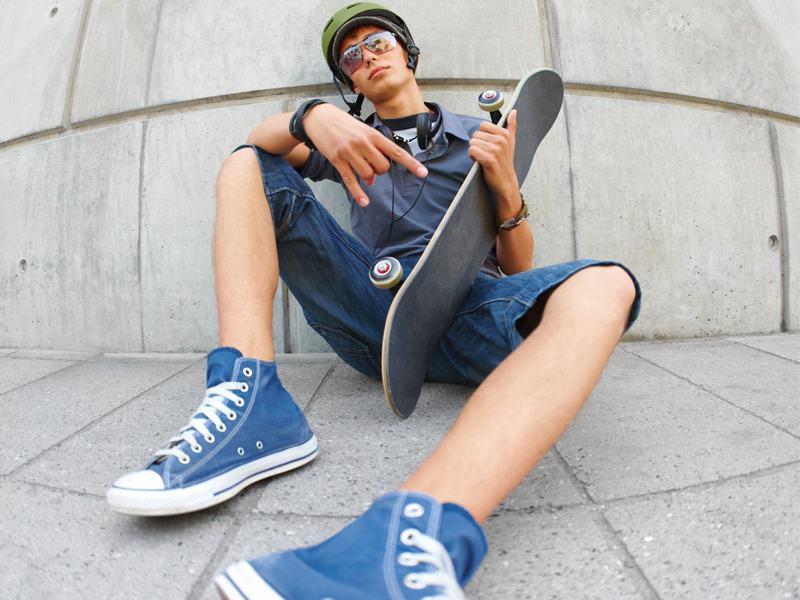 Adolescent assis par terre avec son skateboard en colonie de vacances trottinette