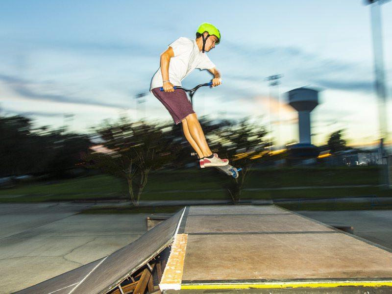 Adolescent pratiquant le saut à trottinette en colonie de vacances