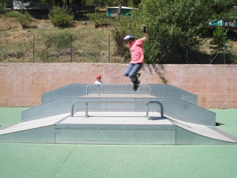 Enfant faisant des sauts en roller au skatepark de colonie de vacances cet été