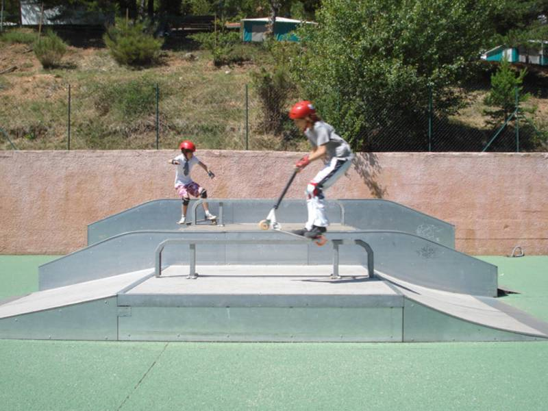 Enfants faisant de la trottinette sur un skatepark en colonie de vacances