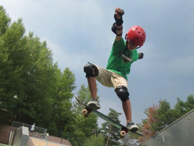 Ado pratiquant le saut en skateboard en colonie de vacances skate cet été