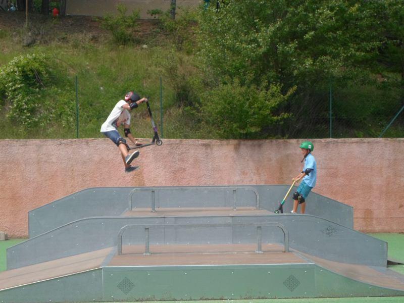 Enfants faisant des sauts en trottinette en colonie de vacances skate