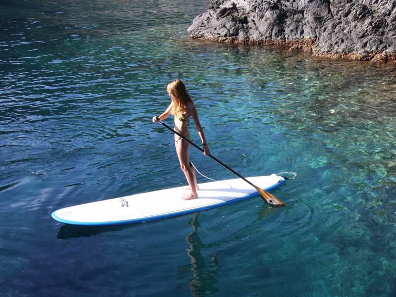Jeune fille sur un stand up paddle se déplaçant sur le lac Sainte Croix à Bauduen en colonie de vacances
