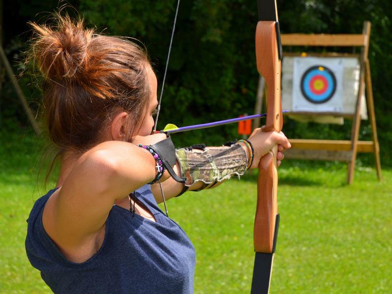 Adolescente visant la cible avec son arc en colonie de vacances multiactivités d'été