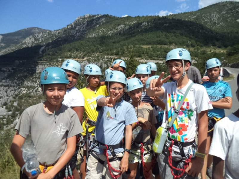 Groupe d'enfants en tenue d'escalade en colonie de vacances d'été multiactivités