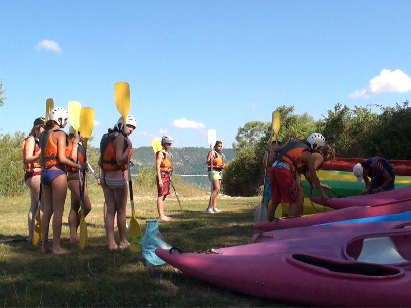 Enfants avec des pagaies s'apprêtant à faire du canoe kayak en colonie de vacances