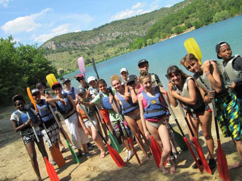 Groupe d'enfants devant le lac de Sainte Croix avec des pagaies et des gilets de sauvetages, prêts à aller faire du canoe kayak en colonie de vacances multiactivités cet été