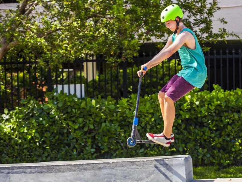 Enfant pratiquant le saut à trottinette en colonie de vacances multiactivités