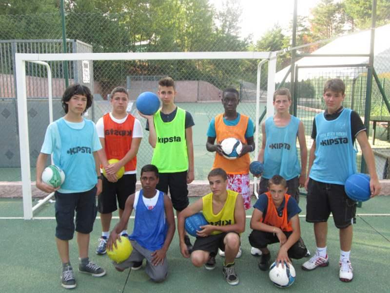 Groupe d'ados posant devant une cage de football en colonie de vacances sportive en été
