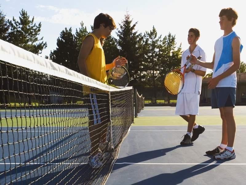 Ados discutant à côté du filet de tennis en colonie de vacances sportive tennis en été