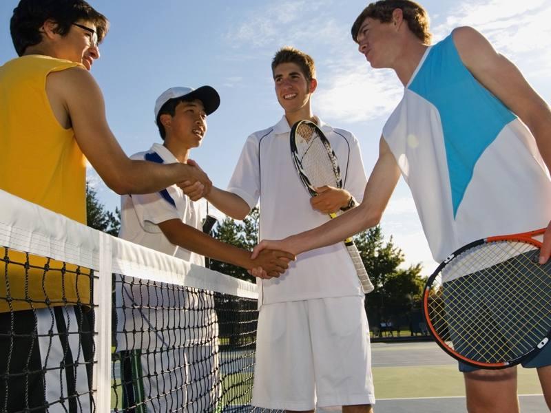 Groupe d'ados en colonie de vacances tennis se serrant la main après un match de tennis