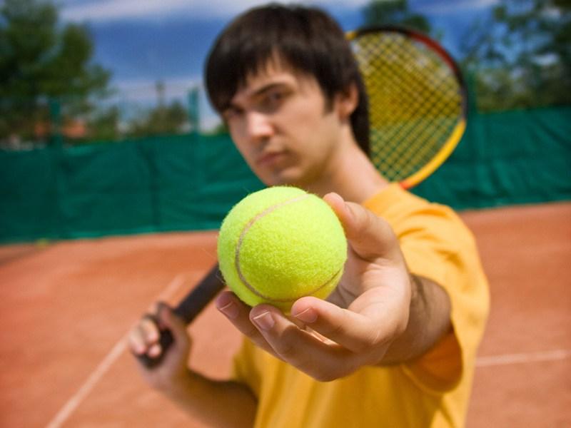 Ados tenant une balle de tennis sur un terrain de tennis en colonie de vacances