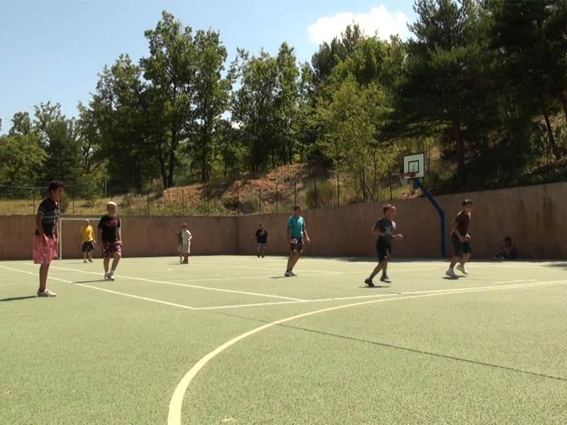 Enfants et ados en colonie de vacances l'été jouant au football sur un terrain de sport