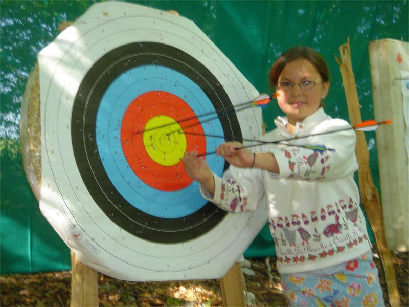 Enfant retirant une flèche d'une cible en colonie de vacances