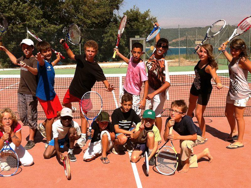 Groupe d'enfants en colonie de vacances tennis sur un court de tennis
