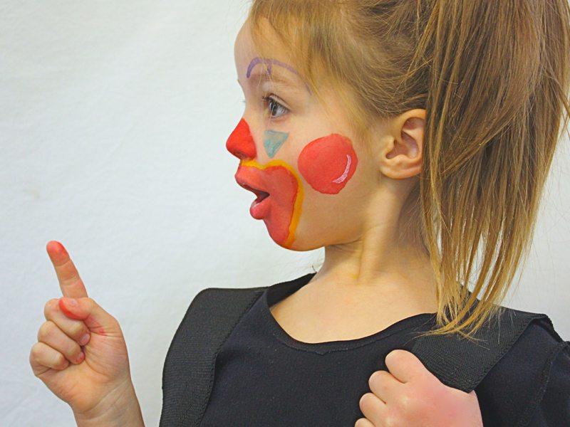 Fillette maquillée en clown jouant la comédie en colonie de vacances d'été