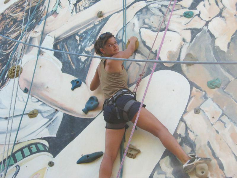 Adolescente grimpant sur un mur d'escalade en colonie de vacances