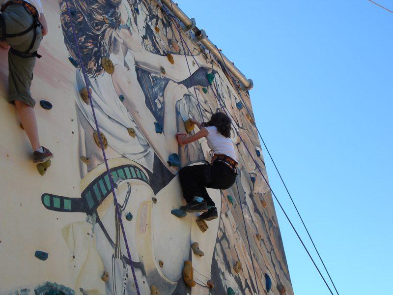 Adolescente grimpant sur un mur d'escalade en colonie de vacances cet été
