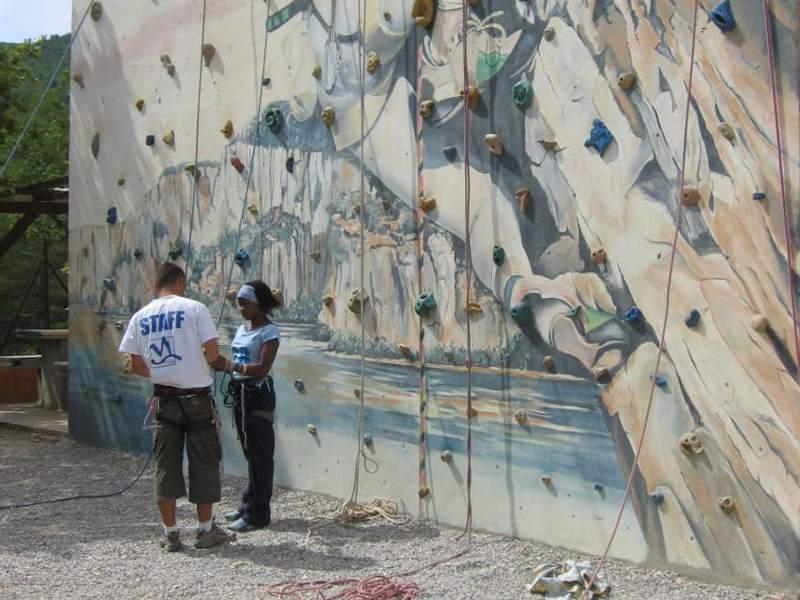 Moniteur d'escalade apprenant à une adolescente à faire de l'escalade en colonie de vacances d'été