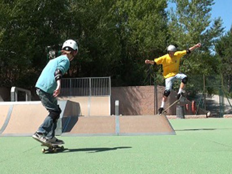 Enfants faisant du roller sur un skate park en colonie de vacances d'été
