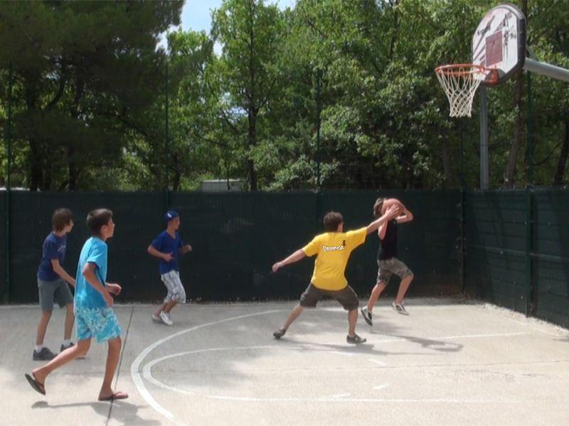 enfants jouant au basketball en colonie de vacances d'été