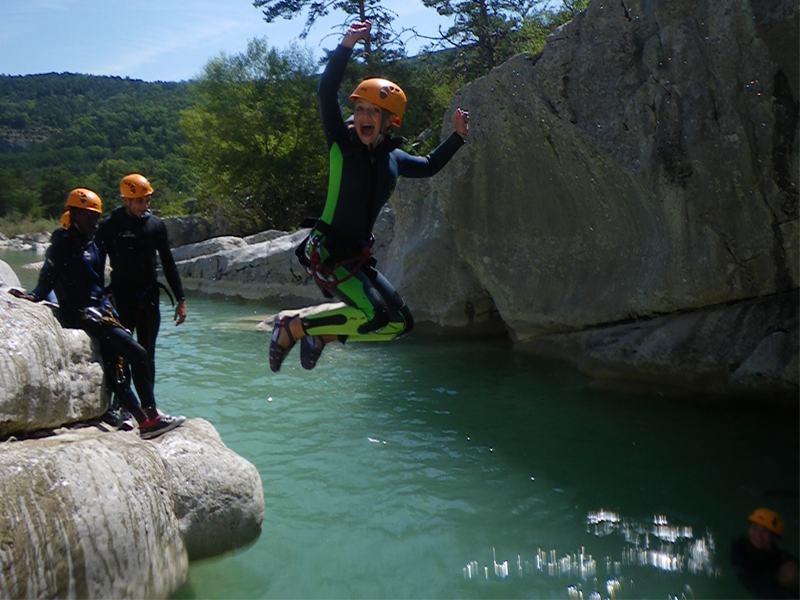 Enfants et ados sautant dans l'eau en combinaison de canyoning en colonie de vacances d'été dans le verdon