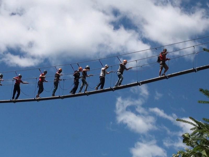 Enfants en colonie de vacances sur un pont de singe évoluant dans les airs
