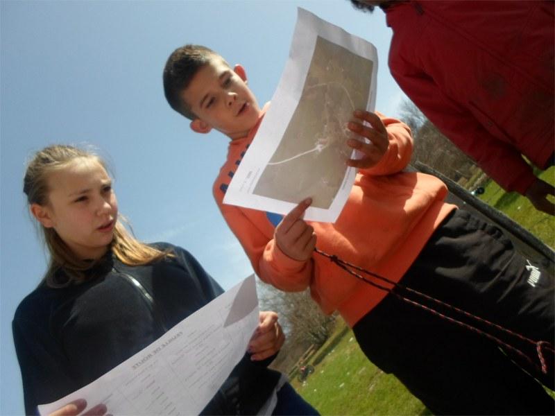Enfants et adolescents en colonie de vacances faisant une course d'orientation