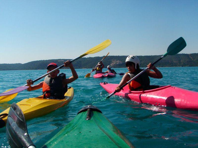 Enfants sur l'eau sur des canoe kayak colorés en colonie de vacances multiacitivités dans le verdon été