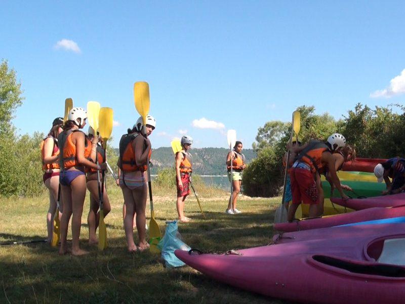 Enfants équipés de pagaie et gilet de sauvetage à côté de canoe kayak en colonie de vacances multiactivités dans le verdon cet été
