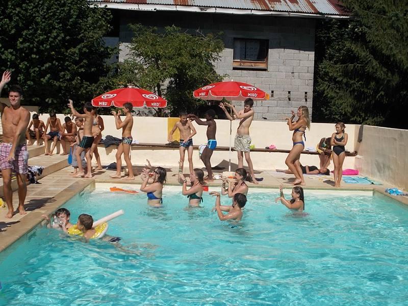 Groupe de jeunes en colonies de vacances en train de se baigner dans une piscine