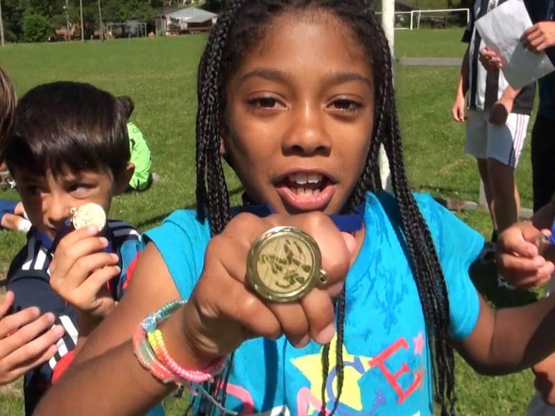 Petite fille qui montre sa médaille de foot