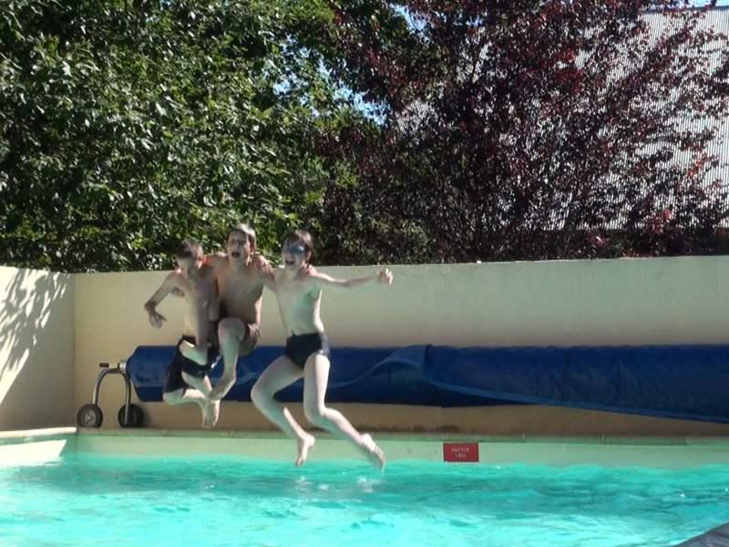 Trois enfants qui sautent dans une piscine