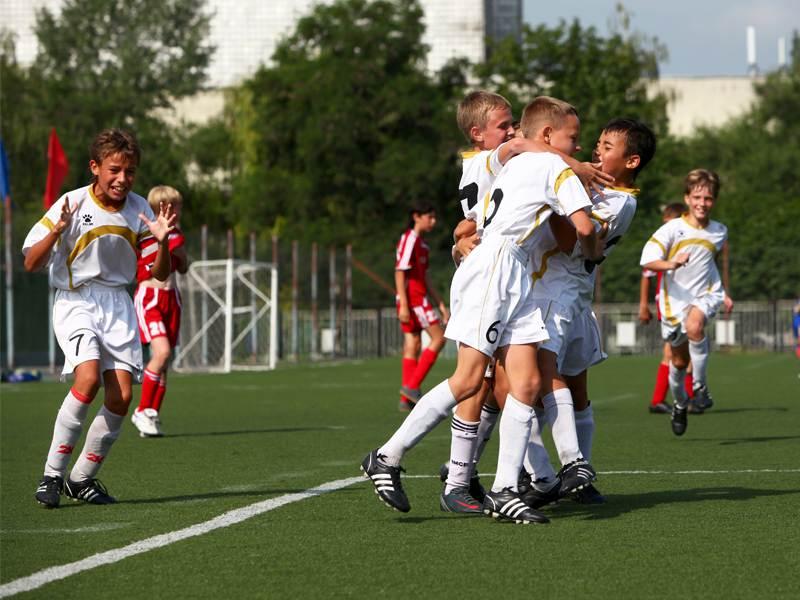Jeunes footballers qui se font une accolade sur un terrain de foot