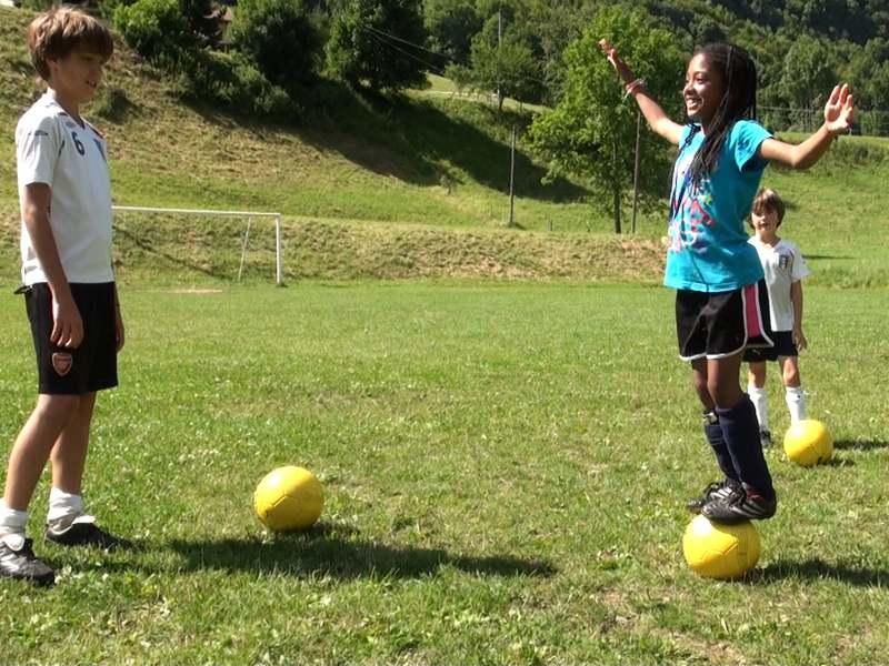 Un garçon et une fille jouant au football