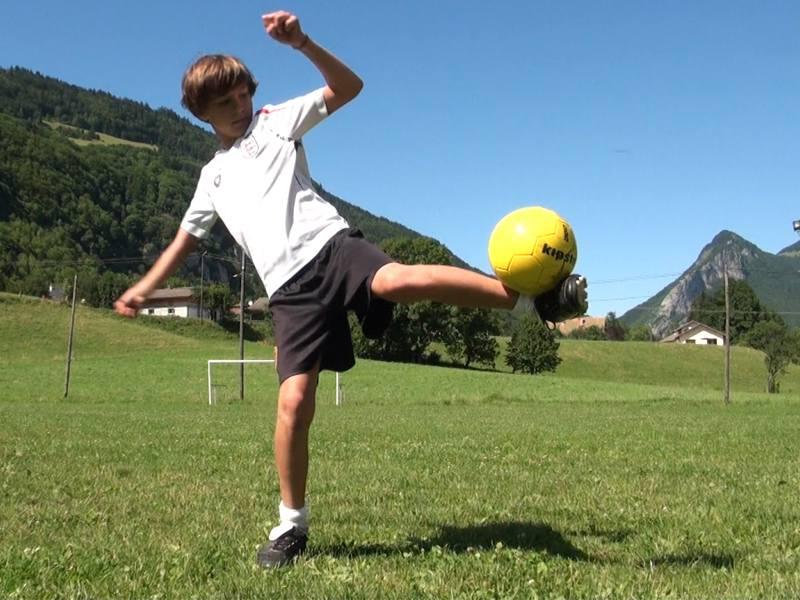 Garçon qui tire sur le ballon de football avec son pied en l'air
