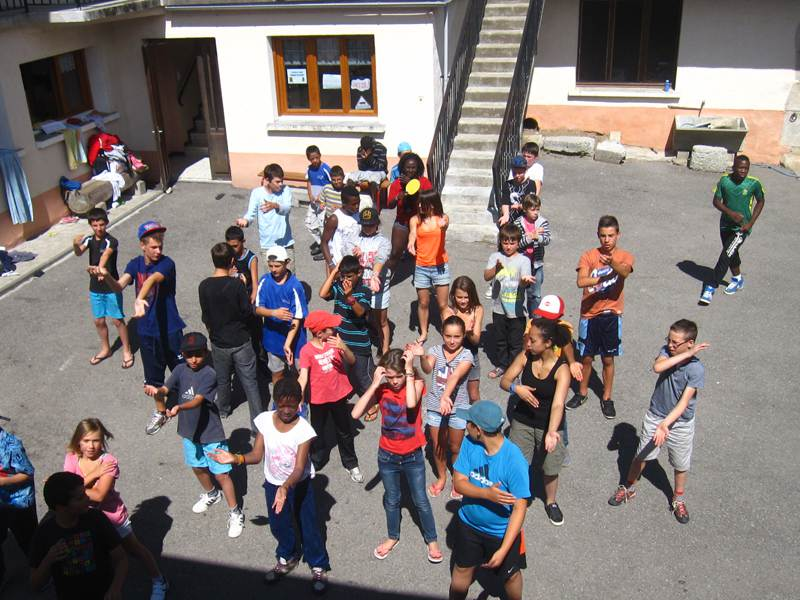 Groupe d'enfants dans une cour en train de danser