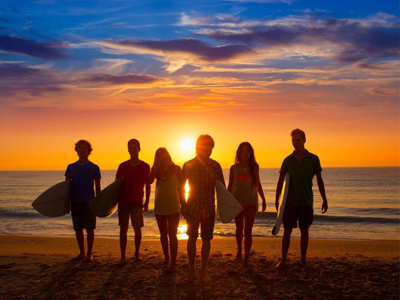 Groupe d'adolescents en bord de mer sous le coucher de soleil avec leur planche de surf en colonie de vacances d'été
