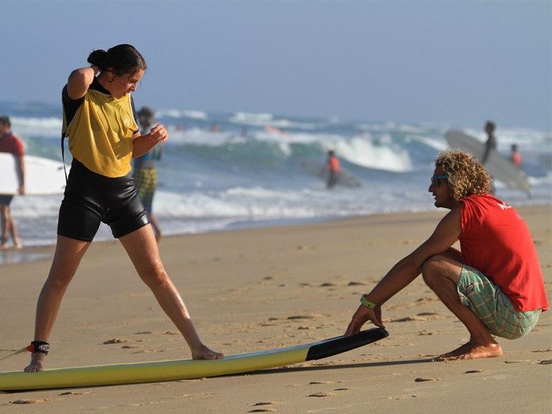 Moniteur de surf apprenant à une adolescente en colonie de vacances à faire du surf