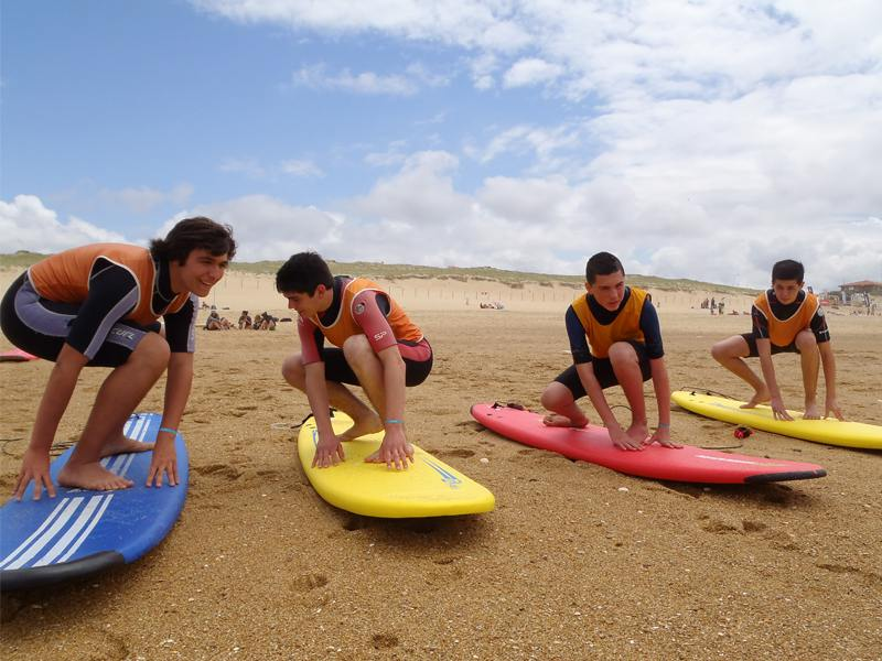 Groupe d'ados sur la plage apprenant à tenir en équilibre sur la planche de surf